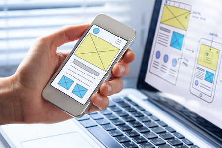 Photo pour Mobile responsive website development with UI/UX front end designer previewing wireframe sketch layout design mockup on smartphone screen - image libre de droit