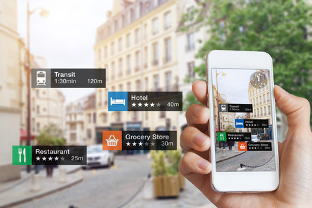 Foto de Augmented Reality (AR) information technology about nearby businesses and services on smartphone screen guide customer or tourist in the city, close-up of hand holding mobile phone, blurred street - Imagen libre de derechos