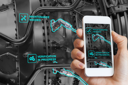 Foto de Augmented Reality technology maintenance and service of mechanical parts, technician using smartphone with AR interface on screen in smart industry, automated monitoring process - Imagen libre de derechos