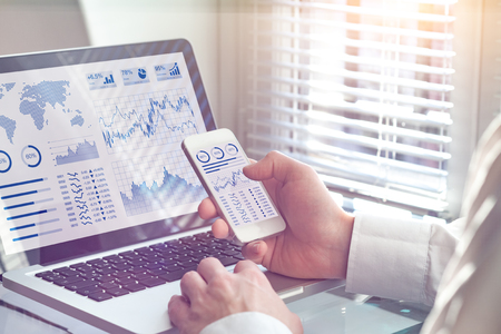 Foto de Business analytics dashboard technology on computer and smartphone screen with key performance indicator (KPI) about financial operations statistics and return on investment, office worker - Imagen libre de derechos