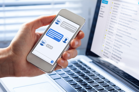 Foto de Chatbot conversation on smartphone screen app interface with artificial intelligence technology providing virtual assistant customer support and information, person hand holding mobile phone - Imagen libre de derechos