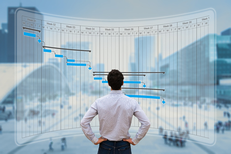 Photo for Project manager working with Gantt chart planning, tracking milestone and deliverables and updating tasks progress, scheduling skills, on virtual screen with city background - Royalty Free Image