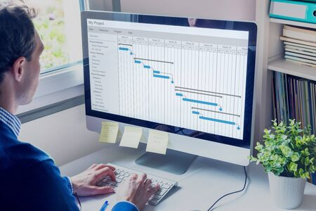 Foto de Project manager working on Gantt chart schedule to create planning with tasks and milestones to plan activities, person working with management tools on computer in office - Imagen libre de derechos