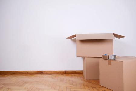 Foto de Stack of cardboard boxes in the empty room with copy space. Move concept - Imagen libre de derechos