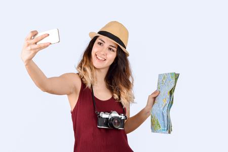 Foto de Portrait of young tourist woman taking a selfie and holding a map on studio. - Imagen libre de derechos