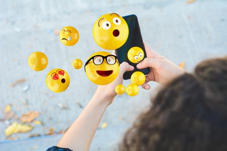 Photo pour Close-up of woman using smartphone sending emojis. Social concept. - image libre de droit