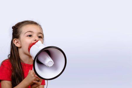 Photo pour Little girl shouting loud holding a megaphone. Communication and sales concept. - image libre de droit