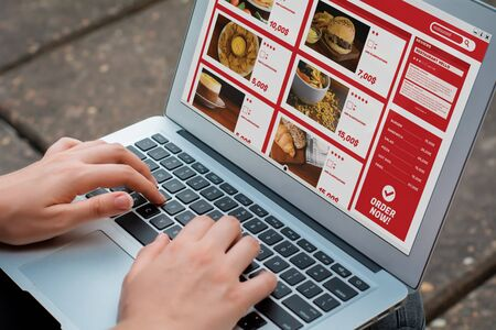 Photo pour Close up woman with laptop ordering take away food online. Delivery concept. All screen graphics are made up by us - image libre de droit