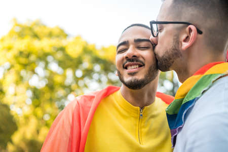 Foto de Portrait of young gay couple embracing and showing their love with rainbow flag in the stret. LGBT and love concept. - Imagen libre de derechos