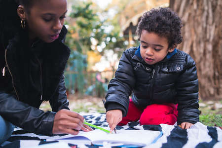 Foto de Portrait of an African american mother with his son playing and having fun together outdoors in the park. Single parent family. - Imagen libre de derechos