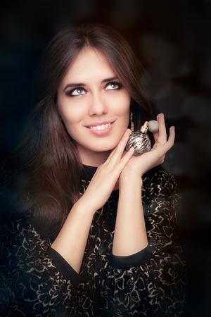 Foto de Retro glamour woman holding vintage perfume bottle - Imagen libre de derechos