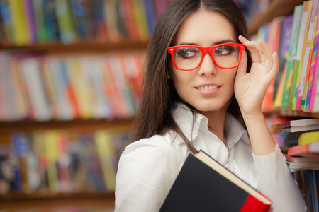 Foto de Portrait of a woman with red eyeglasses holding a book in a library - Imagen libre de derechos