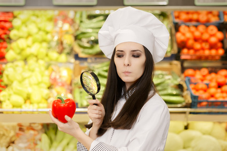 Photo pour Concerned  Lady Chef Inspecting Vegetables with Magnifying Glass - image libre de droit