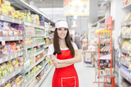 Photo for Smiling Supermarket Employee Standing Among Shelves - Royalty Free Image