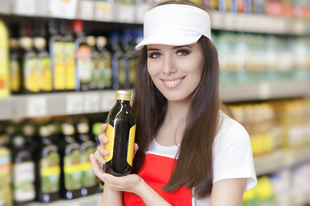 Photo for Smiling Supermarket Employee Holding a Product - Royalty Free Image