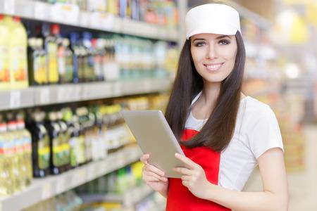 Photo pour Smiling Supermarket Employee Holding a Pc Tablet - image libre de droit