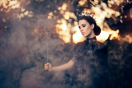 Photo pour Evil Queen Holding Scepter in Misty Forest - image libre de droit