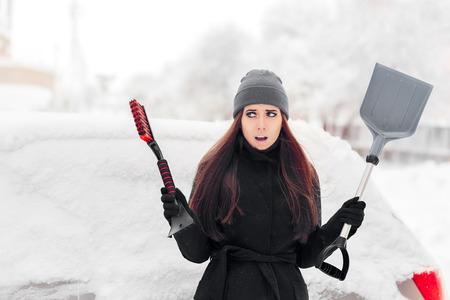 Foto de Girl with Brush and Shovel Removing Snow from the Car - Imagen libre de derechos