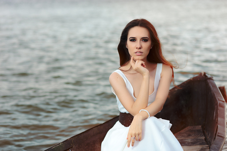Photo for Thoughtful Woman in White Dress Sitting in an Old Boat - Royalty Free Image