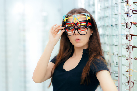 Photo for Funny Woman Trying Many Eyeglasses Frames in Optical Store - Royalty Free Image