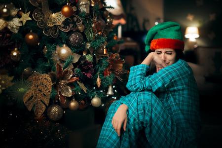 Foto de Sad Upset Lonely Girl Crying Next to Her Christmas Tree - Imagen libre de derechos