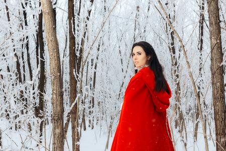 Foto de Beautiful Red Riding Hood Princess in Magic Winter Forest - Imagen libre de derechos