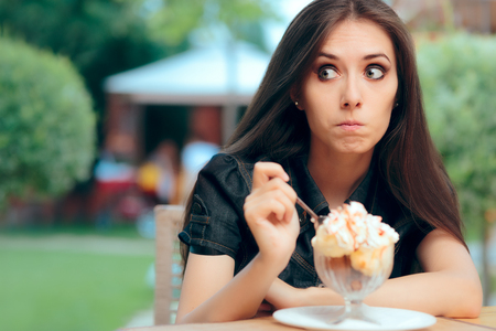 Photo for Girl Heisting to a Eat High Calorie Ice Cream Dessert - Royalty Free Image