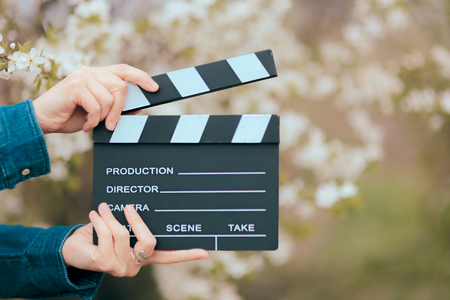 Photo pour Hands Holding Film Slate Cinema Clapper on Spring Blooming Background - image libre de droit