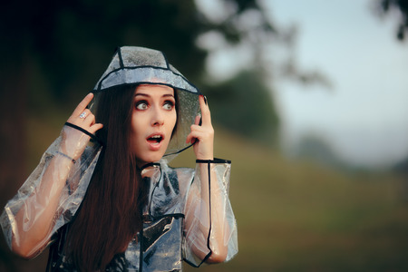 Foto de Surprised Woman in Clear Transparent Raincoat in Summer Rain - Imagen libre de derechos