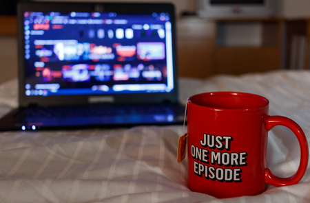 Foto de Watching series with a cup of tea. Inscription Just one more episode. Millennial concept - Imagen libre de derechos