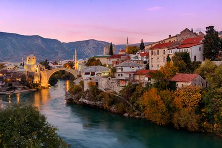 Foto de Skyline of Mostar with the Mostar Bridge, houses and minarets, at the sunset in Bosnia and Herzegovina.p - Imagen libre de derechos