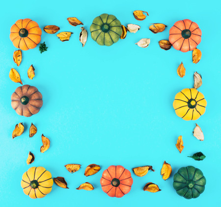 Photo for Decorative pumpkins on trendy blue background with fall leaves frame. - Royalty Free Image