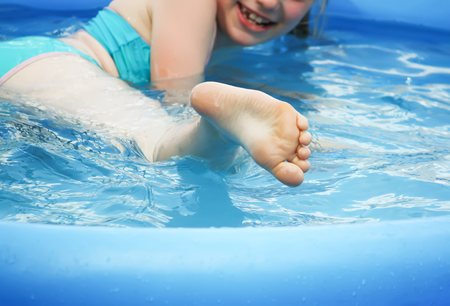 Photo for Little girl playing and spraying water in swimming pool outdoors at summer. - Royalty Free Image