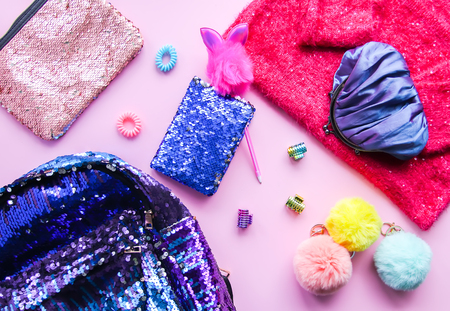 Photo for Bright composition of fashion accessories and dress. Glitter sequins sweetshot, purse, backpack, colorful pompons and hair bands. Different objects on soft pink pastel background. Flat lay, top view. - Royalty Free Image
