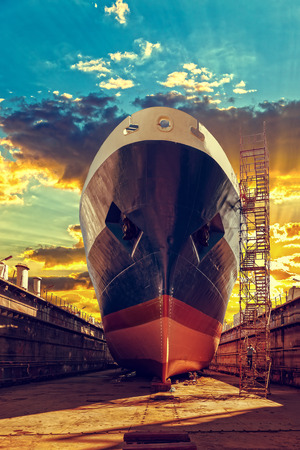 Photo for Ship in dry dock at sunrise - shipyard in Gdansk, Poland. - Royalty Free Image