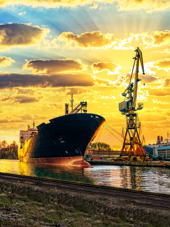 Photo for Cargo ship and the port at sunset. - Royalty Free Image