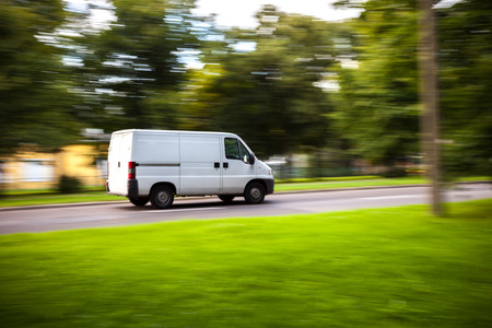 Foto de White delivery van speeding on road with blurred countryside panorama in background. - Imagen libre de derechos