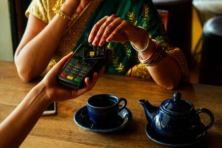 Photo for Young indian businesswoman in green traditional sari on a coffee break. Using payment terminal paying by credit card in a cafe restaurant.black friday sale - Royalty Free Image