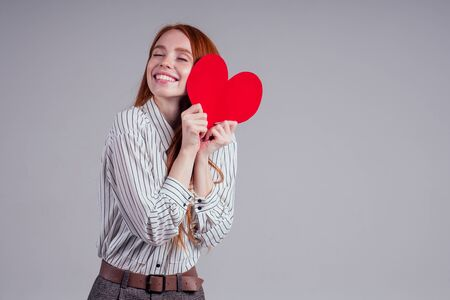 Photo for Happy redhead girl businesswoman in a striped shirt model sending air kiss with decorative hearts Valentines Day gift on white background studio - Royalty Free Image