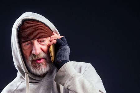 Photo pour portrait of sad old senior male tramp wearing warm brown hat and leaky gloves,talking by smartphone in studio black background - image libre de droit