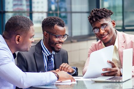 Foto de A group of three stylish African American businessman partners entrepreneurs in fashion business suits meeting sitting at table sign securities with laptop in a summer cafe outdoors - Imagen libre de derechos