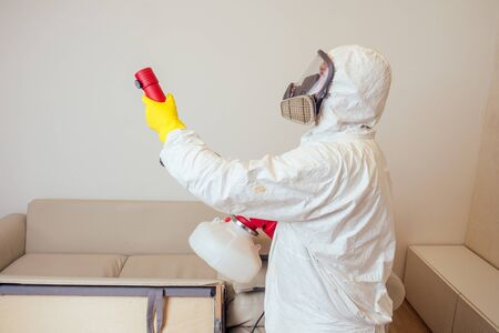 Foto de pest control worker in uniform spraying pesticides under couch in living lounge room - Imagen libre de derechos
