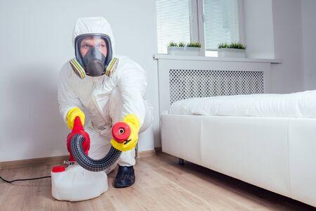 Foto de pest control worker lying on floor and spraying pesticides in bedroom - Imagen libre de derechos