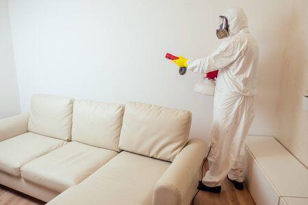 Foto de pest control worker in uniform spraying pesticides under couch in living lounge room. - Imagen libre de derechos