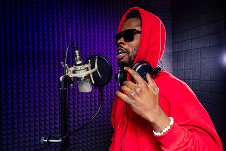 Photo for afro american man headphones in a cap and a hood sunglasses recording hip hop song track. - Royalty Free Image