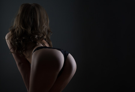 Photo pour Young woman in lingerie posing back studio shot on dark bg - image libre de droit