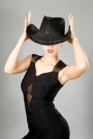 Portrait of the young girl in an elegant black dress and a hat