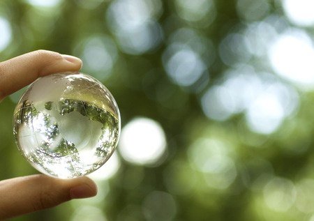 Foto de World environmental concept. Crystal globe in human hand on beautiful green bokeh. Visible are the continents the Americas - Imagen libre de derechos