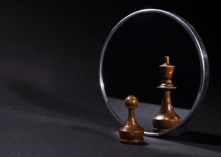 Foto de Pawn looking in the mirror and seeing a king. Black background. - Imagen libre de derechos