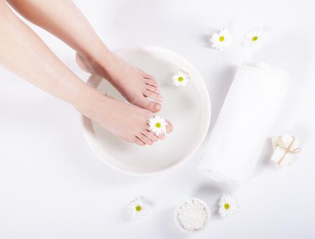 Foto de Female feet with spa bowl, towel and flowers on white background - Imagen libre de derechos
